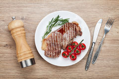 Sirloin steak with rosemary and cherry tomatoes on a plate Royalty Free Stock Images