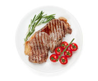 Sirloin steak with rosemary and cherry tomatoes on a plate. Isolated on white background Royalty Free Stock Photos