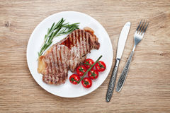 Sirloin steak with rosemary and cherry tomatoes on a plate Stock Photography