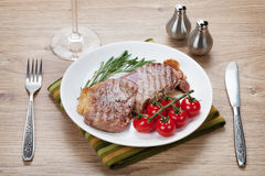 Sirloin steak with rosemary and cherry tomatoes on a plate Stock Photo