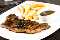 Sirloin steak. Served with black pepper sauce and French fries Royalty Free Stock Photo