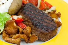 Sirloin strip steak with baked potato and chantere Royalty Free Stock Photos
