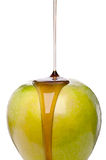 Sirop d'érable étant plu à torrents sur une pomme verte Photos libres de droits