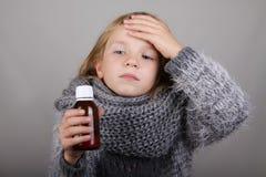 Sirop de toux de participation de petite fille de cheveux blonds dans une main Enfant malade Concept de soins de santé de grippe  photographie stock
