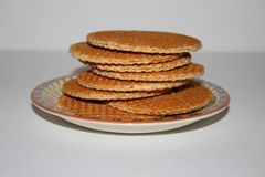 Siropwafels dutch cookies on isolated white background. Syrup waffles dutch stacked on a porcelain dish traditional cookies dessert on white isolated background Stock Image
