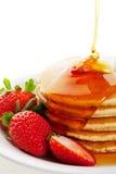 Sirup, der auf Pfannkuchen gießt lizenzfreies stockfoto