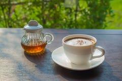 Sirup und Kaffee auf einer hölzernen Tabelle mit einem natürlichen Hintergrund stockbilder
