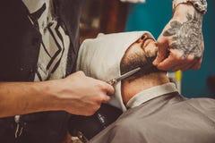 Sirva afeitar su barba en el peluquero profesional Fotos de archivo