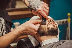 Sirva afeitar su barba en el peluquero profesional Imagen de archivo libre de regalías
