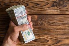 Sirva agarrar una pila gruesa de 100 billetes de dólar Foto de archivo