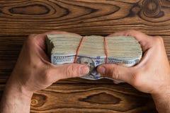 Sirva agarrar una pila gruesa de 100 billetes de dólar Imágenes de archivo libres de regalías
