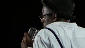 Sirva al afroamericano joven la visión desde la parte posterior que se acerca al micrófono que canta en un estudio de grabación n metrajes