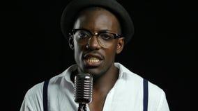 Sirva al afroamericano joven que canta en un micrófono en un estudio de grabación Fondo negro Cierre para arriba metrajes