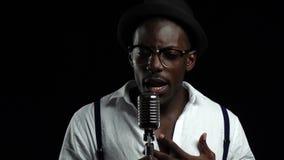 Sirva al afroamericano joven que canta en un micrófono en un estudio de grabación Fondo negro Cámara lenta Cierre para arriba almacen de metraje de vídeo