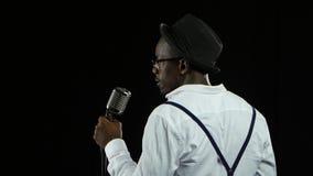 Sirva al afroamericano la visión desde la situación trasera en el micrófono que canta profesionalmente en un estudio de grabación metrajes