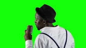 Sirva al afroamericano la visión desde la situación trasera en el micrófono que canta profesionalmente en un estudio de grabación almacen de metraje de vídeo