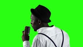 Sirva al afroamericano la visión desde la parte posterior en el micrófono que canta profesionalmente en un estudio de grabación P almacen de video