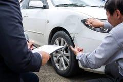 Sirva al agente coche cerca dañado y de examen de Filling Insurance Form, imagen de archivo libre de regalías