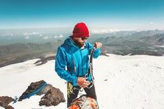 Sirva al alpinista con el hacha de hielo que sube en montañas Imagenes de archivo