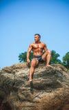 Sirva al atleta en una roca por el mar Fotografía de archivo libre de regalías