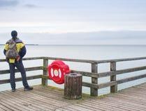 Sirva al caminante con la mochila en topo mojado sobre el mar Mañana brumosa con agua lisa Imagenes de archivo