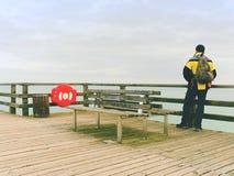 Sirva al caminante con la mochila en topo mojado sobre el mar Mañana brumosa con agua lisa Foto de archivo libre de regalías