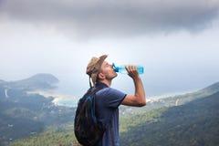 Sirva al caminante en un top de una montaña, bebidas riegan Recorrido a Tailandia concepto de una forma de vida sana foto de archivo