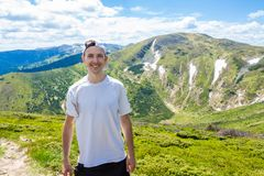 Sirva al caminante que se relaja en el top de la colina y que admira la opinión hermosa del valle de la montaña Fotos de archivo