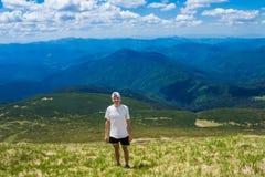 Sirva al caminante que se relaja en el top de la colina y que admira la opinión hermosa del valle de la montaña Foto de archivo