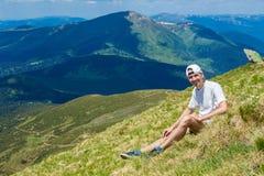 Sirva al caminante que se relaja en el top de la colina y que admira la opinión hermosa del valle de la montaña Fotos de archivo libres de regalías