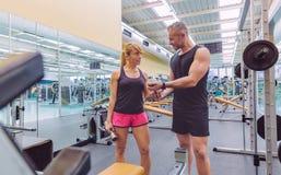 Sirva al coche que ayuda a la mujer en el entrenamiento de las pesas de gimnasia Foto de archivo