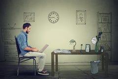 Sirva al empresario que trabaja en el ordenador portátil en la oficina que se sienta en silla fotografía de archivo