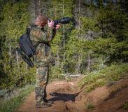Sirva al fotógrafo en equipo del camuflaje con una mochila y un trípode que se colocan en un rastro y tirar del bosque de la mont Fotos de archivo