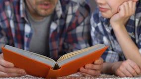 Sirva al hijo del libro de lectura que explica el tema de escuela, ayuda con la preparación, conocimiento almacen de video
