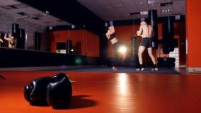 Sirva al instructor tailandés del boxeo que ejercita con la mujer joven, entrenando a luchar para la autodefensa almacen de video