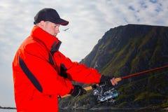 Sirva al pescador en una chaqueta roja con las manos udobkoy Fotos de archivo libres de regalías