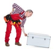 Sirva al técnico con la caja de elevación del metal del dolor de espalda Foto de archivo libre de regalías