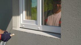 Sirva al trabajador en las gafas de seguridad que barren la superficie para la instalación del travesaño del metal de la ventana  almacen de video