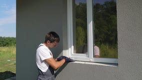 Sirva al trabajador en las gafas de seguridad que limpian la superficie para la instalación del travesaño del metal de la ventana metrajes