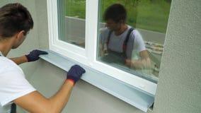 Sirva al trabajador en los guantes protectores que miden tamaño externo del travesaño del metal del marco y de la ventana del PVC almacen de video