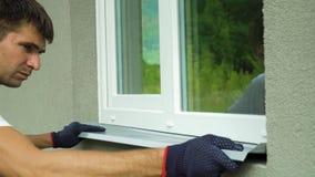 Sirva al trabajador en los guantes protectores que miden tamaño externo del travesaño del metal del marco y de la ventana del PVC metrajes