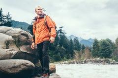 Sirva al viajero con la mochila en la orilla del río de la montaña Foto de archivo libre de regalías