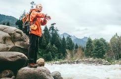 Sirva al viajero con la mochila en la orilla del río de la montaña Fotografía de archivo