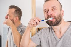 Sirva aplicar sus dientes con brocha en cuarto de ba?o imagen de archivo libre de regalías