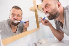 Sirva aplicar sus dientes con brocha en cuarto de ba?o imagenes de archivo