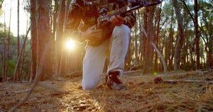 Sirva apuntar con el arco compuesto en el bosque 4k almacen de metraje de vídeo