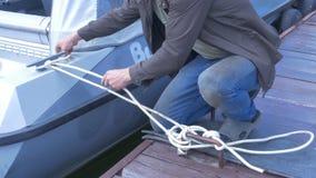 Sirva atar la cuerda de barco en la playa con el fondo del mar foto de archivo libre de regalías
