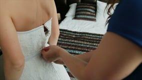 Sirva atar un corsé en el vestido de boda del ` s de la novia almacen de video