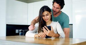 Sirva besar a la mujer mientras que usa el teléfono móvil 4k almacen de video