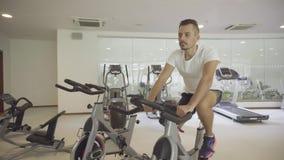 Sirva biking en el gimnasio, ejercitando sus piernas que hacen las bicis de ciclo del entrenamiento cardiio metrajes